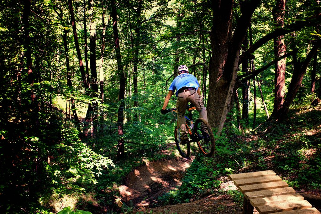 Mountain biker Daniel Goldbach goes off a jump into a deep ravine at Harmonie State Park's Mountain Bike Trail.
