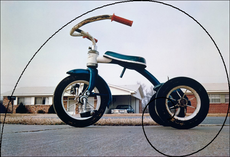 Eggleston photo of red tricycle with golden ration overlay